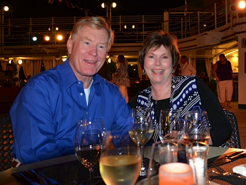 Boomer man and woman smiling at a table at an outdoor party on a cruise ship.