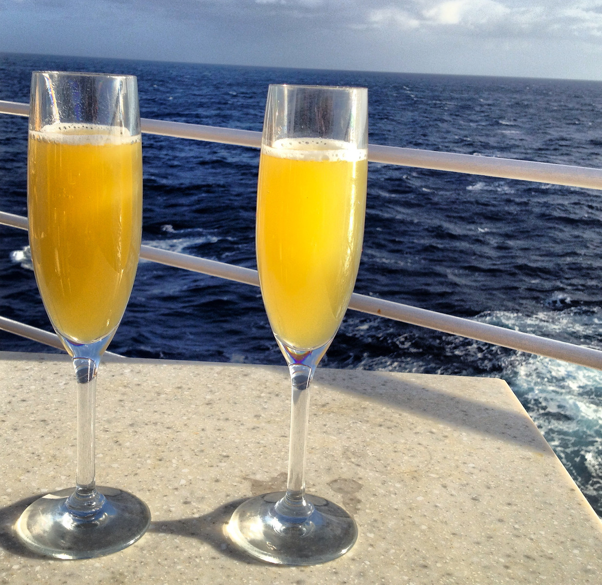 Mimosas served in champagne glasses on the balcony of a cruise ship.
