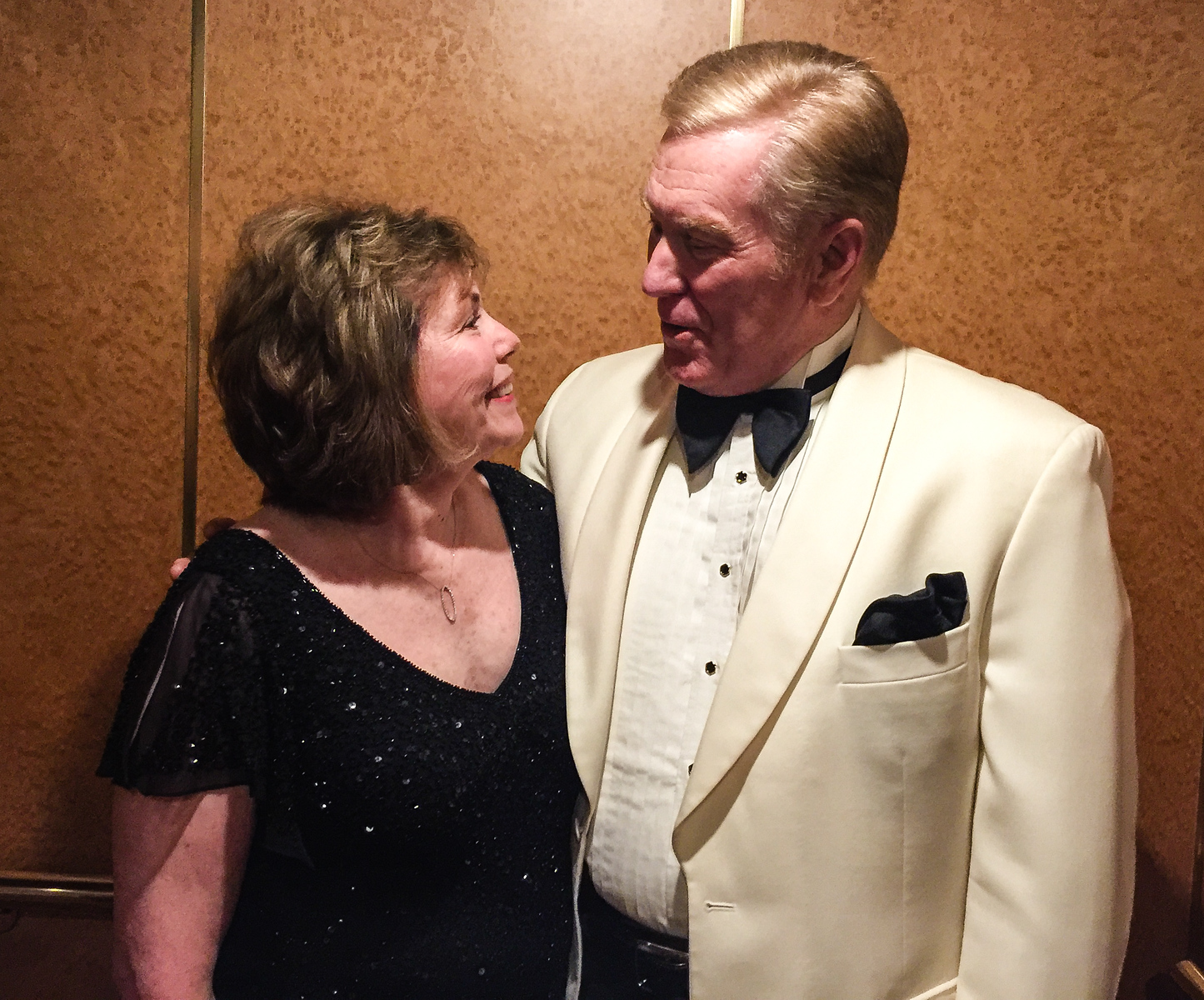Boomer woman and man in formal clothes, reconnecting on a cruise.