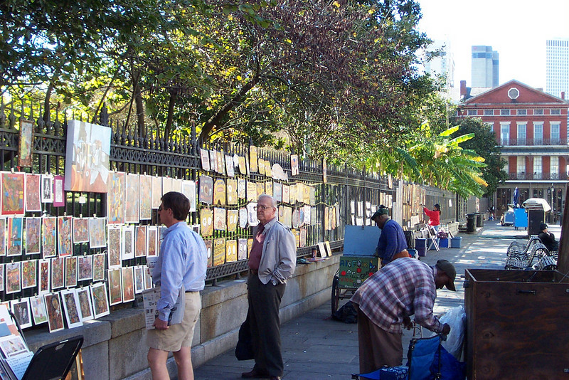 Across from the cathedral, artists were setting up their masterpieces to sell to tourists like us.  Dad checked out the art, but we didn't buy anything.  The fence around Jackson Square makes a good easel!<br /> [New Orleans]