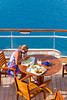 A lady having lunch on an outside deck on the Celebrity cruise ship Millennium.