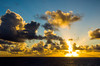 Sunset with clouds and sunburst over the Atlantic Ocean.