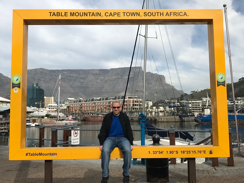 """Speaking of high quality... for our stays in Cape Town, Victoria Falls, Johannesburg & Krueger Park... AMA put us up at great hotels! In Cape Town for example we stayed at the """"Cape Grace Hotel"""" which is the redish/orange hotel over Shawn's shoulder. It's in the heart of the """"Victoria & Alfred Waterfront"""" which is the main tourist area in Cape Town and it's best feature is the amazing views of """"Table Mountain"""" that all of AMA's guests had from their rooms."""