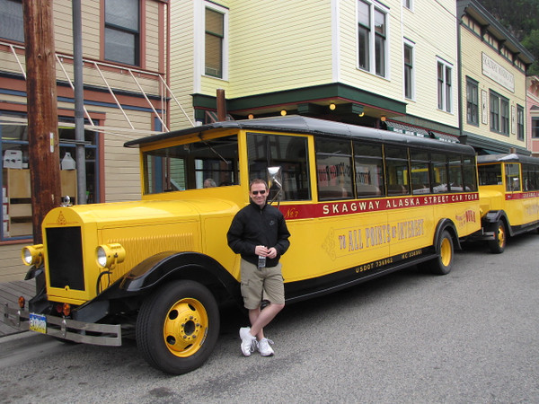 "There's Shawn posing by an old style Skagway street car... if you want to learn about the town's famous ""Gold Rush"" history make sure to do the tour in one of these beauties to learn all about it."