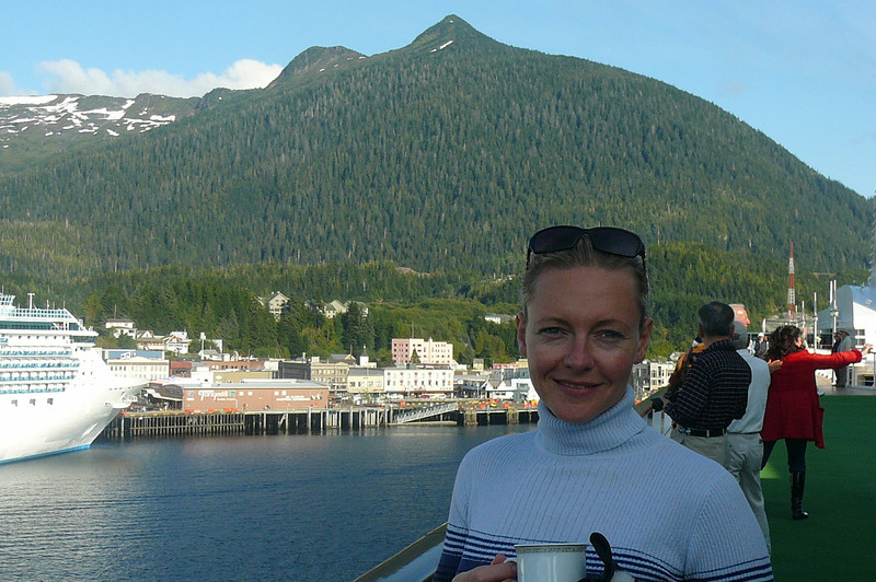 "Here's Nancy enjoying a cup of Coffee with ""Deer Mountain"" and Ketchikan in the background as we head back out to Sea through ""Tongass Narrows""."