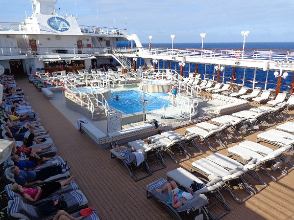 """There's a super popular place, the Main Pool. If you look closely you'll notice super comfortable & quality loungers along with thick cushions on them & over sized towels... that's the quality difference you'll experience on a small ship line like Azamara Club Cruises compared to the big ships... as well, with higher quality food, service & no crowds, it makes for a true """"Dream Cruise Vacation!"""" :-)"""