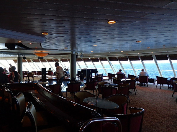 "Sorry about the Dark pic but the main feature of the ""Looking Glass"" Lounge up on Deck 10 is it's floor to ceiling windows (which you can see people enjoying above) & have some quiet time during the day as you watch the World go by. Oh, don't forget to head there at night time for a little dancing... Fun!! :-)"