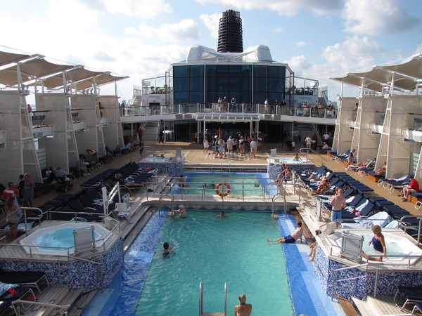 "There's a glimpse of the ""Solstice's"" Pool area... a very nice design compared to a typical ship as it had huge Cabanas on both decks providing lots of shade for those hot, hot days!"