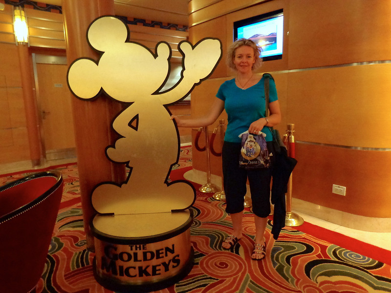 """There's Nancy checking out a life-size """"Golden Mickey"""", Disney's version of the """"Academy Awards/Oscars"""" that celebrates Disney's biggest hits when it comes to their many famous animated movies.<br /> <br /> You can read our full blog post review here about our amazing Cruise on the """"Disney Wonder"""": <a href=""""http://nancyandshawnpower.com/disney-wonder-cruise-review/"""">http://nancyandshawnpower.com/disney-wonder-cruise-review/</a>"""
