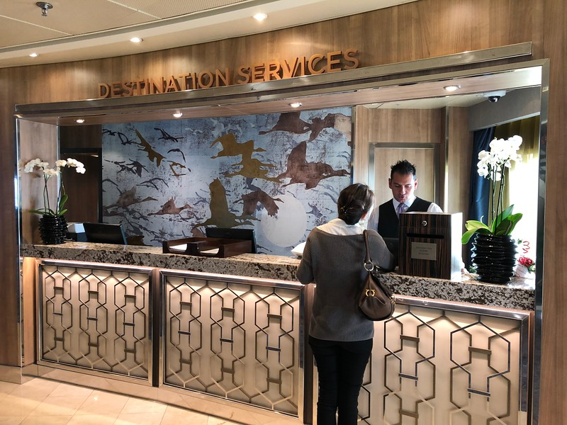 """Alright, the last picture we wanted to show you onboard was the """"Destination Services"""" desk… on Regent, it's a more important place then on all the other Ocean lines since Regent includes Shore Excursions in their prices. (that's a super rarity in the Cruise Industry outside of River Cruises) So, you'll be meeting these people on your port days as they make sure your excursion start times are organized, they help you make changes, etc.<br /> <br /> FYI, best to book your excursions online in advance (again, Shawn will let you know what date that is for your booking) to get all your choices confirmed before you step onboard. BUT, if one of the tours you want is waitlisted when you go to book online don't panic and go ahead and waitlist yourself… once onboard pretty much 100% of the time the """"Destination Services"""" Team will get you on the tour you want as guests are constantly making changes. For example, on this Cruise we had 7 tours booked but cancelled 2 of them once onboard which opened up space for others so it's rare you won't get on the tours you want."""