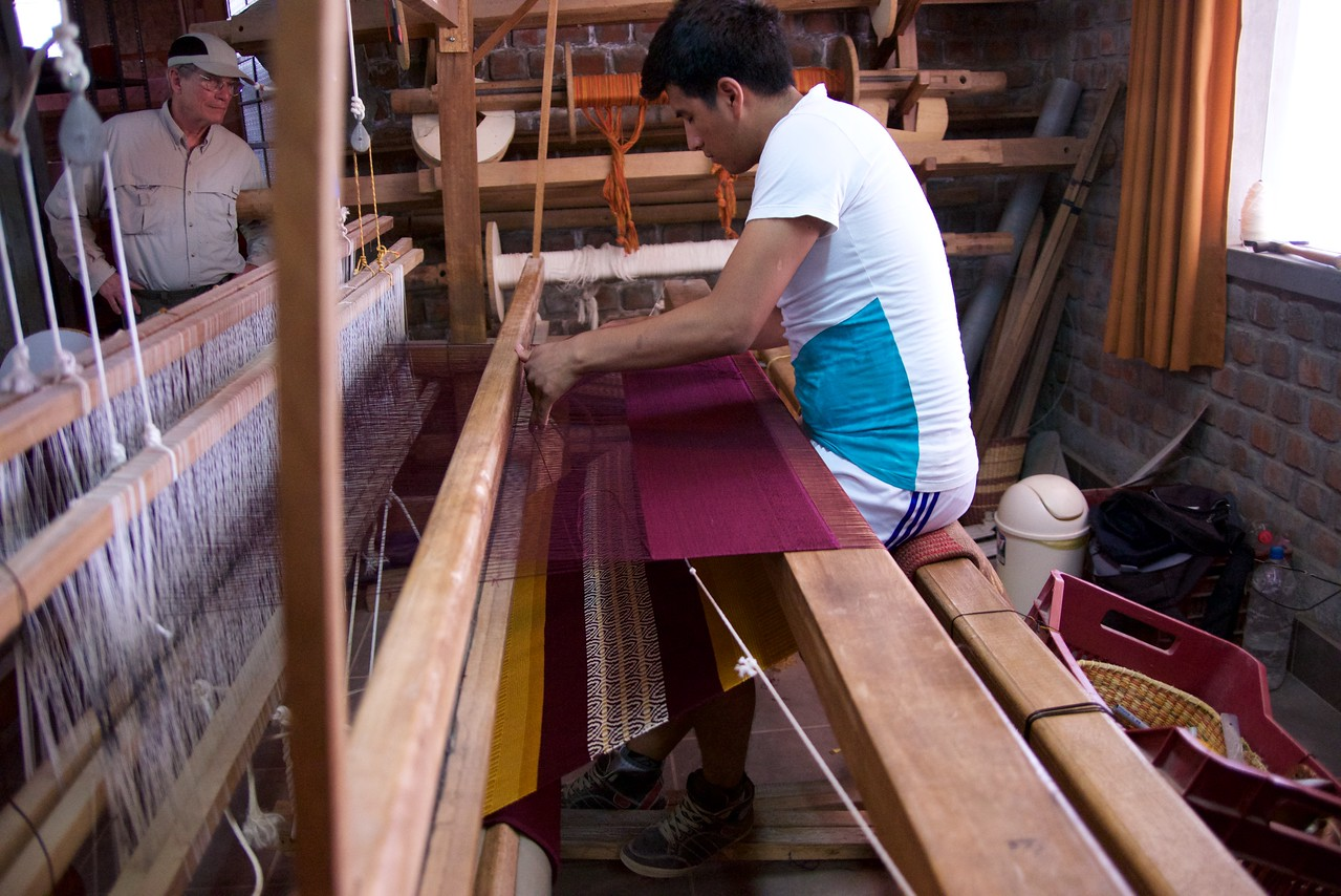 Men and women work on the weaving