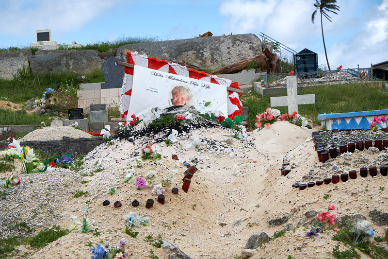 This is a typical cemetery on Tonga. The stone in the upper left is a Royal Tomb which is why it is elevated and stands alone.