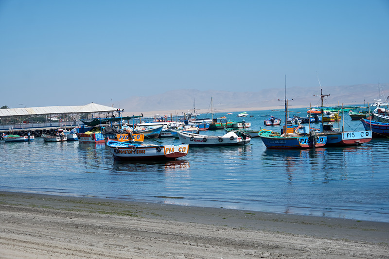 Paracas seaside with dirty sand beaches and a faint outline of the desert mountains in the far background.