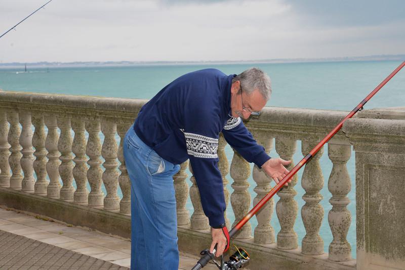 Fisherman Adjusting His Pole.