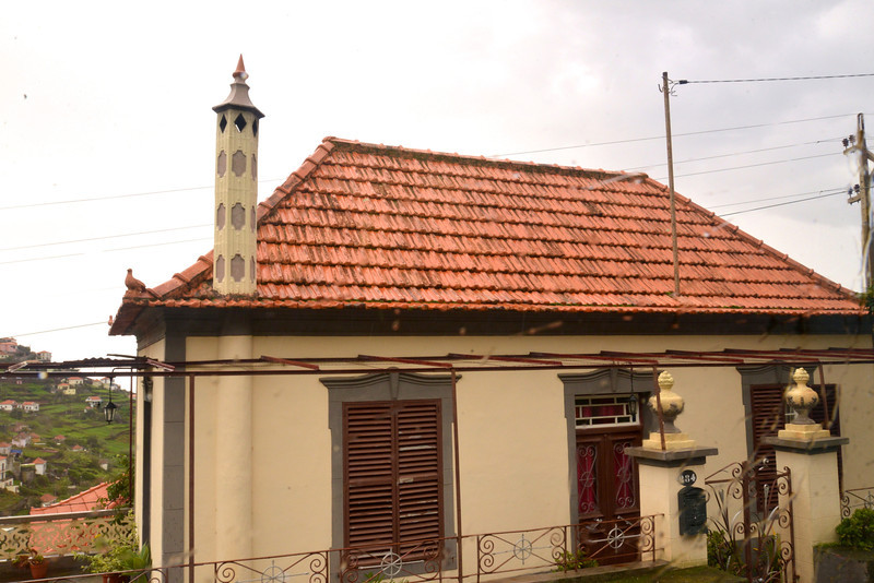 Madeira Does Not Have A Specific Type of Architecture House Have Certain Elements- (1) Hip Tiled Roof for Drainage, (2) Beige, Yellow or White Walls, (3) Shuttered Windows and (4) Birds or Faces on Four Corners of Roof… Guards from Evil Spirits.