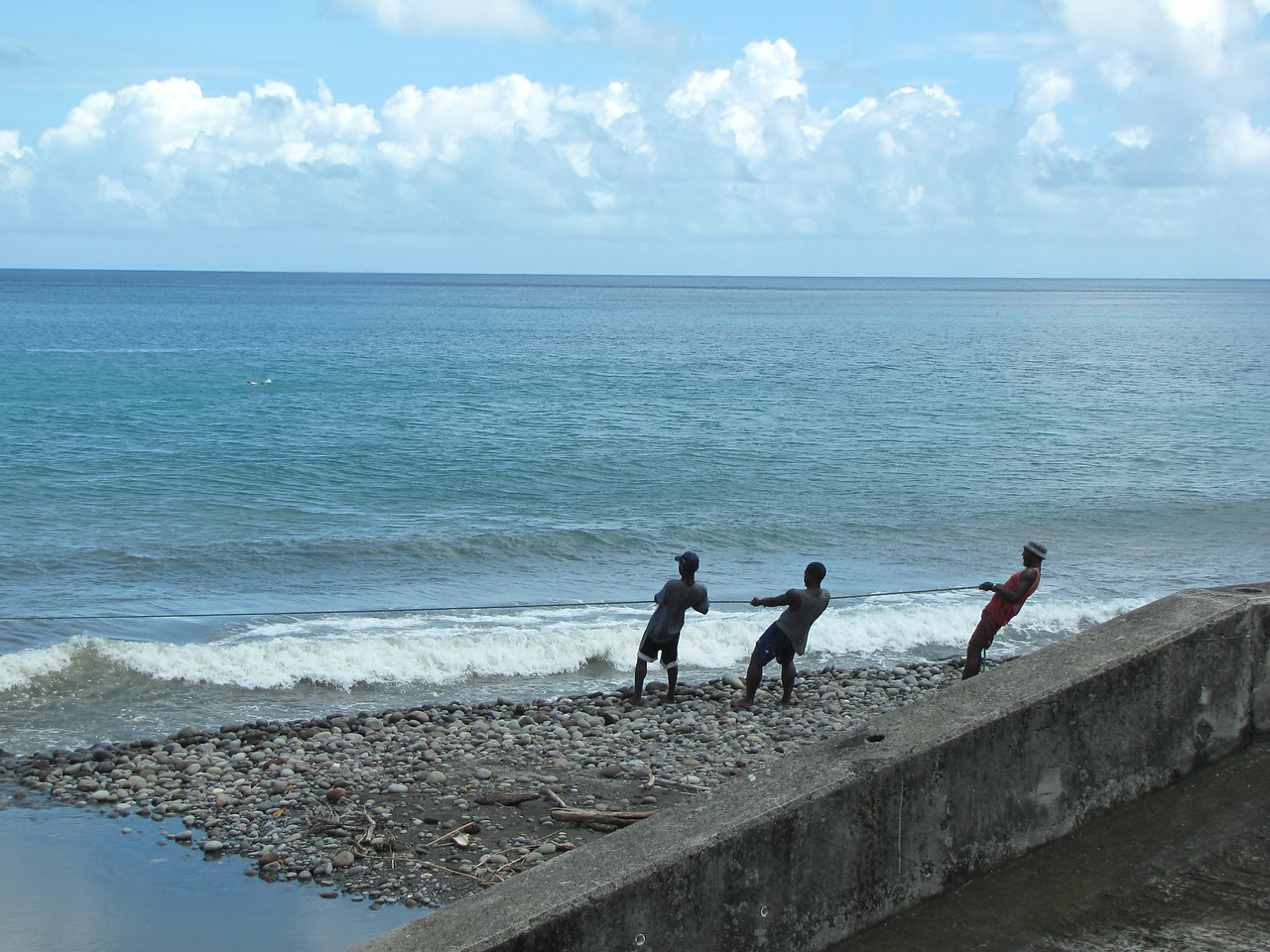 Fishermen hauling in a large net.