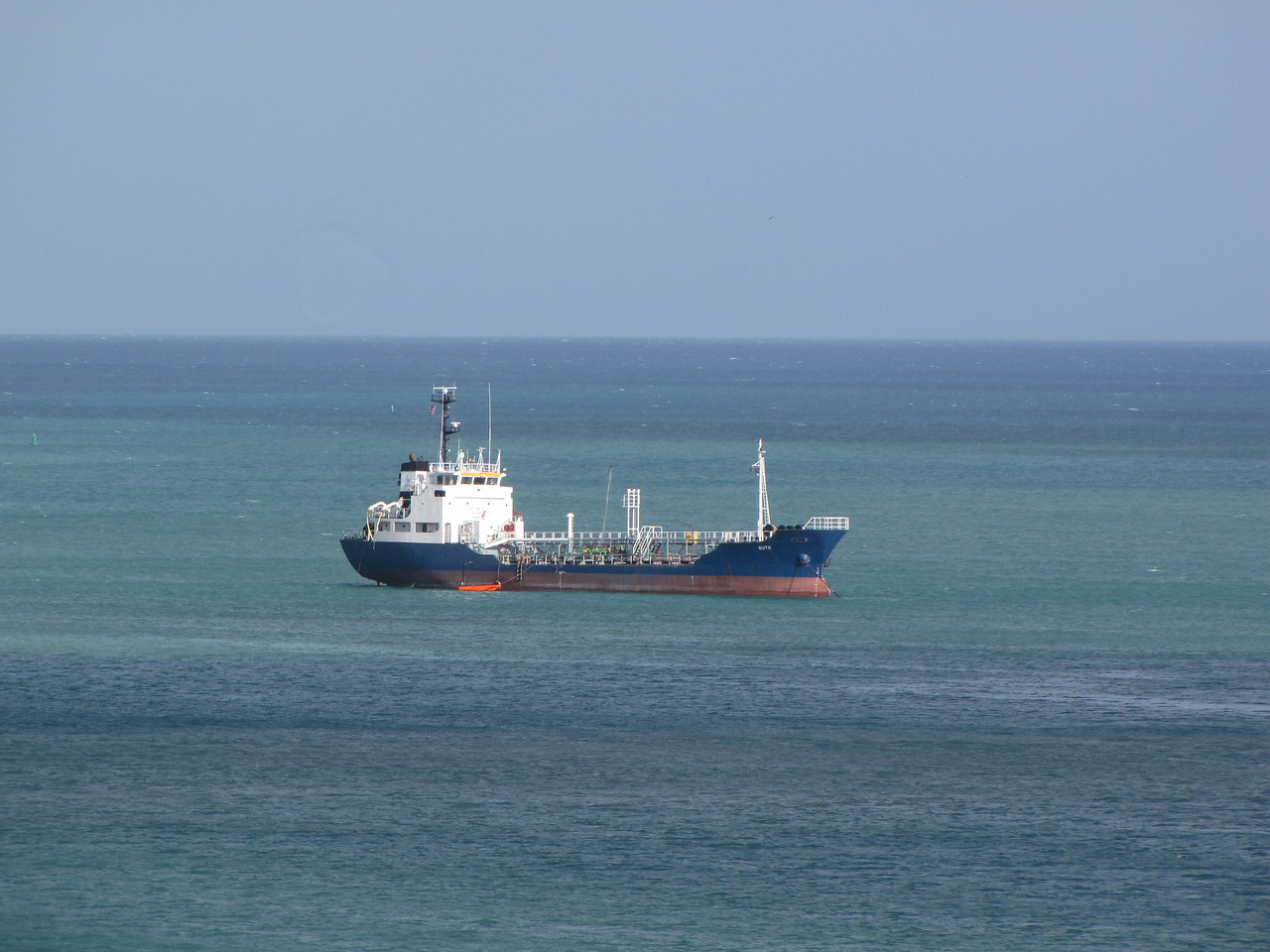 A lone tanker is anchored at the entrance to the harbour.