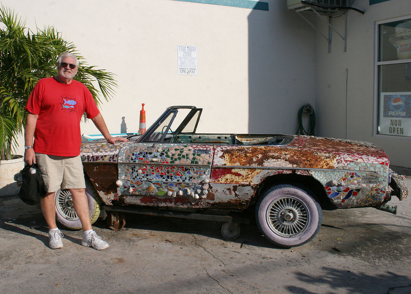 Notice the rusted car Mike is standing next to and the mosaic they are putting on.