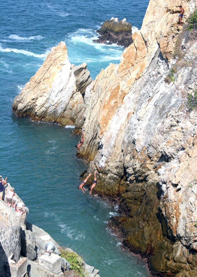 Cliff Divers about to enter the water