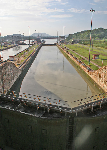 Mira Flores Locks.  All the lock chambers in the Panama Canal are 110 ft wide by 1050 ft long. Ships are raised or lowered a total of 85 ft.  On the Atlantic side, the three steps of the Gatun locks is 85 ft; the lift of the two-step Mira Flores locks (which is where we are now) is 54 ft. The lift at Mira Flores actually varies due to the extreme tides on the Pacific side, between 43 ft at extreme high tide and 64.5 ft at extreme low tide; the tides on the Atlantic side, however, are very small.<br /> <br /> The lock chambers are massive concrete structures. The side walls are from 45 to 55 feet thick at the bases; towards the top, where less strength is required, they taper down in steps to 8 ft. The center wall between the chambers is 60 ft thick, and houses three long galleries which run the full length of the center wall. The lowest of these is a drainage tunnel; above this is a gallery for electrical cabling; and towards the top is a passageway which allows operators to gain access to the lock machinery.