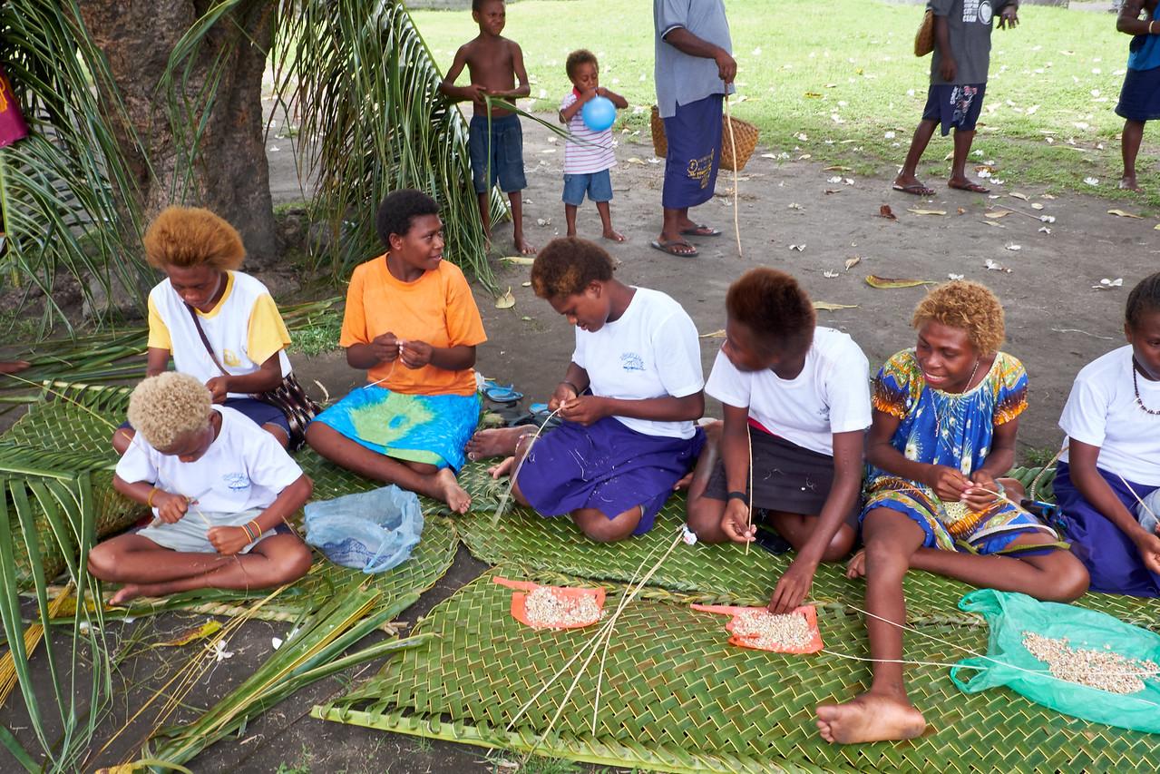 Girls stringing money shells.