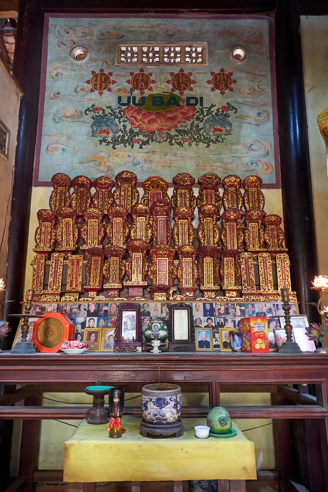 The gilded wooden carvings on the top are the names of monks who have died. The women pictured have died and their children brought the pictures so the monk will pray for them so that they will get to heaven.