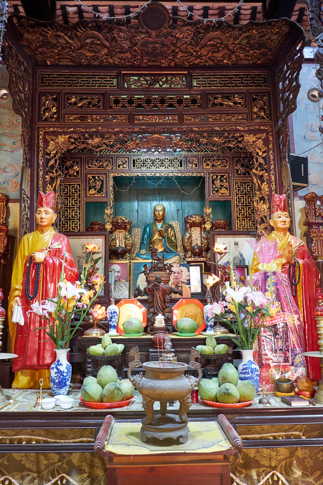 The figure in the center is the monk who founded The Main Buddha in the Vinh Trang Pagoda. This is an active Pgoda and there are resident monks. The main chamber is made of dark wood pillars and has gilt woodwork.