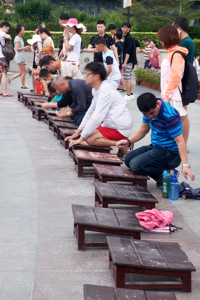 People actively praying to Guan Yin Statue.