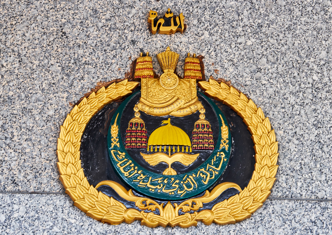 The Sultan's personal crest. Allah rules above all, followed by the Sultan (crown) who pledges to protect people with honor and dignity (umbrella, wings), his written pledge as well as his pledge to provide for his people (rice sheafs).
