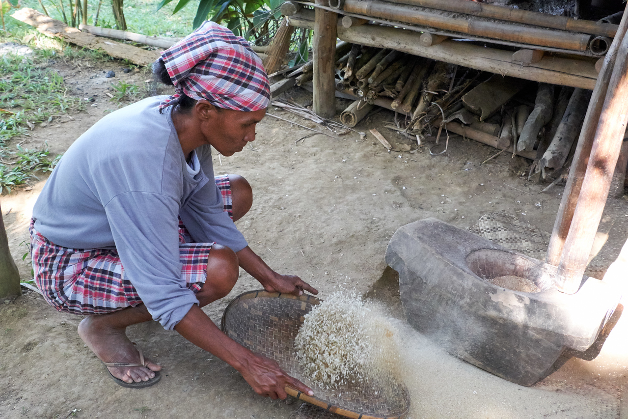 Cleaning the ground rice with a bamboo sieve.