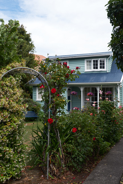 A smaller cottage. The rose arbor leads into the front garden.