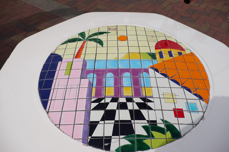 Example of the tile mosaic on the octagonal seats along the shopping street.