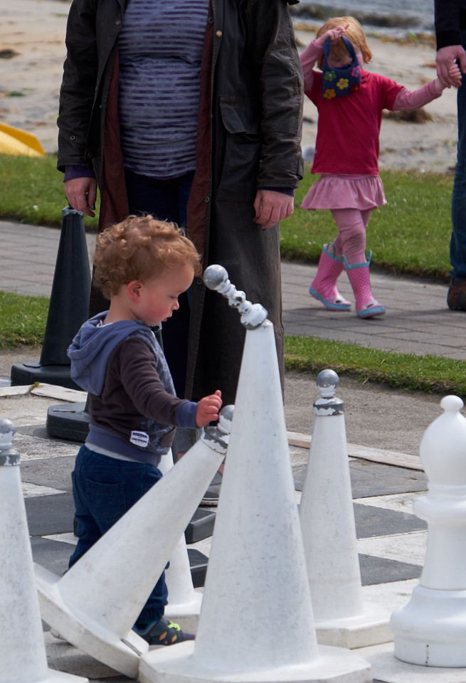 This little boy kept knocking over the chess pieces.