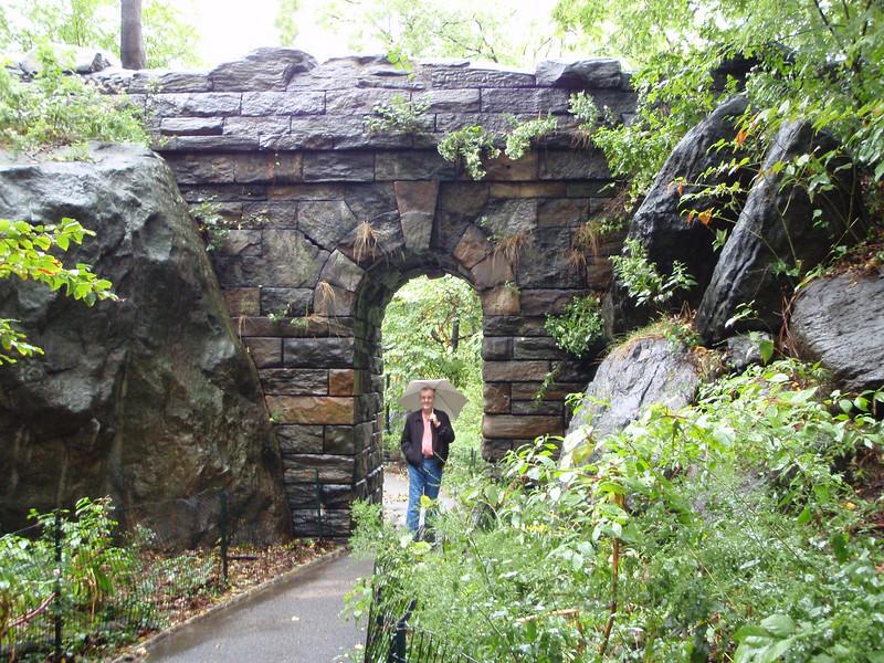 Kenny walks under a stone arch bridge.