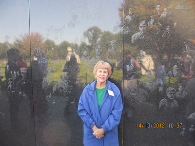 Statues at the Korean War Memorial are reflected on a black granite wall, which is etched with photos of American soldiers who fought in the war.
