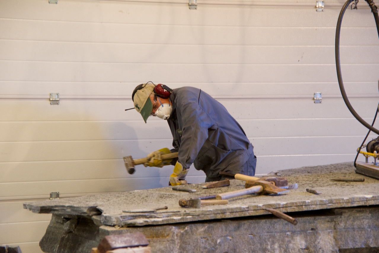 """Trond hammers metal pegs into the """"mica"""" layer of the slate to separate it"""