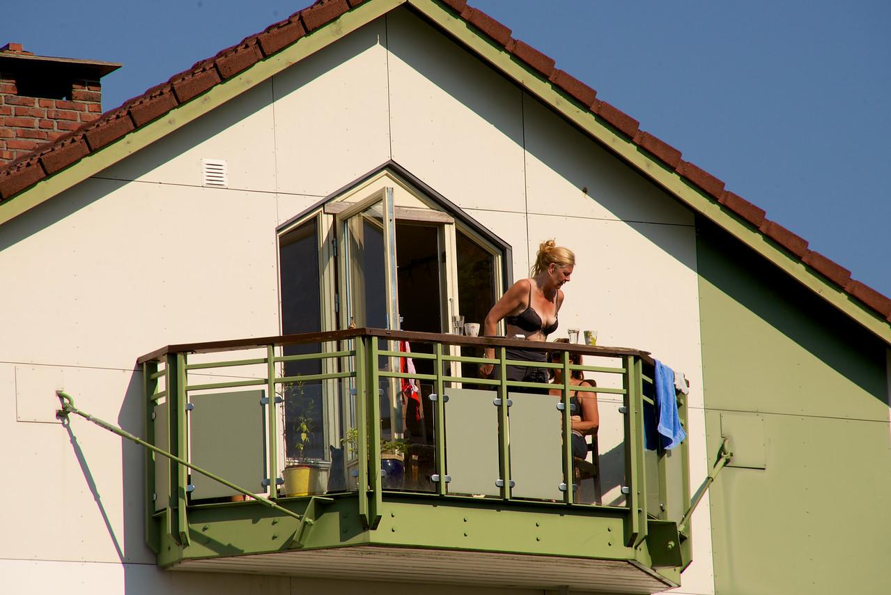 Locals spending the morning sunbathing on their apartment veranda