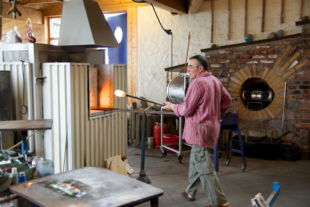 Taking hot molten glass out of the fire and over to the colored pieces