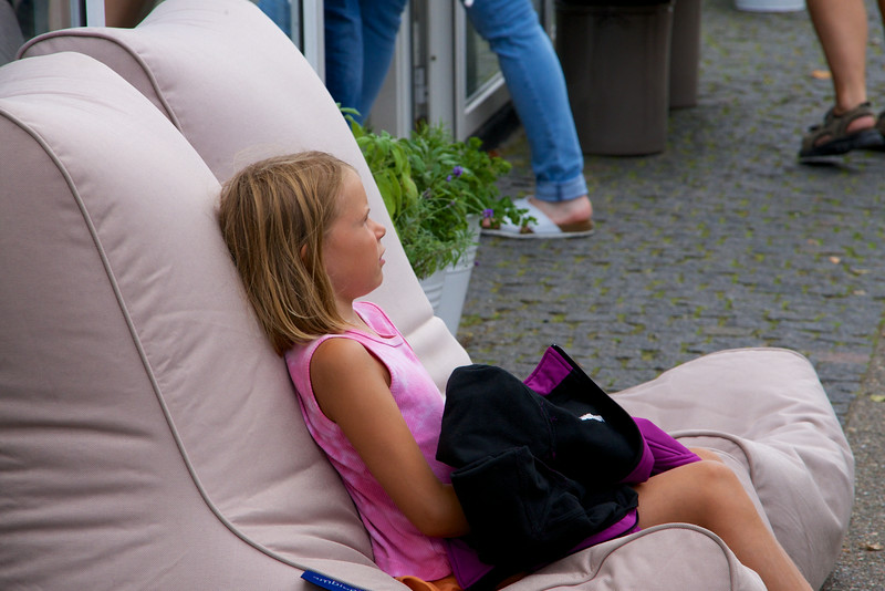 Little girl testing out the merchandise   chairs in front of the store