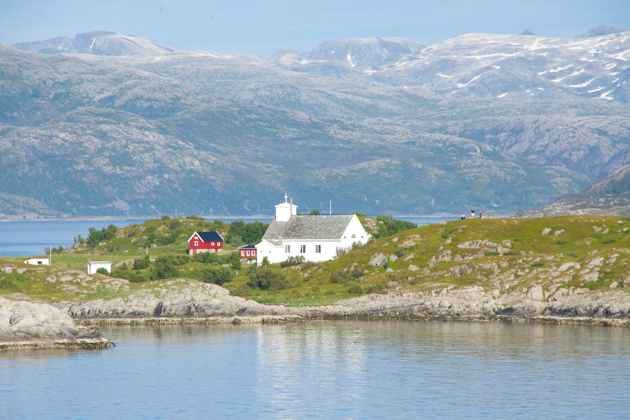 This island was seen during Symphony's sail out of fjord. There was a single house, a single church, a cemetery and a light of sorts on the island along with at least 3 people (seen in the picture).