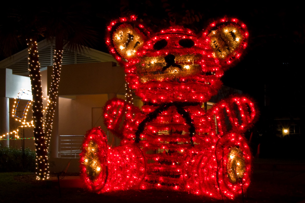 The red teddy bear is the centerpiece of the Christmas light display.