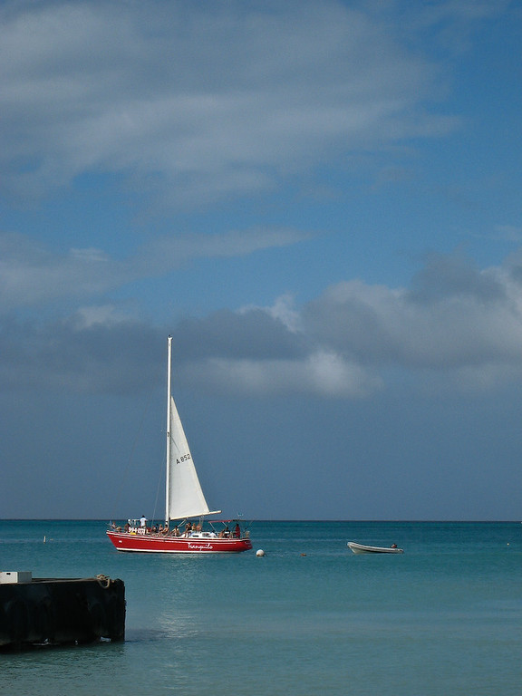 A red sailboat adds a splash of color against the blues and greens of the sky and sea.