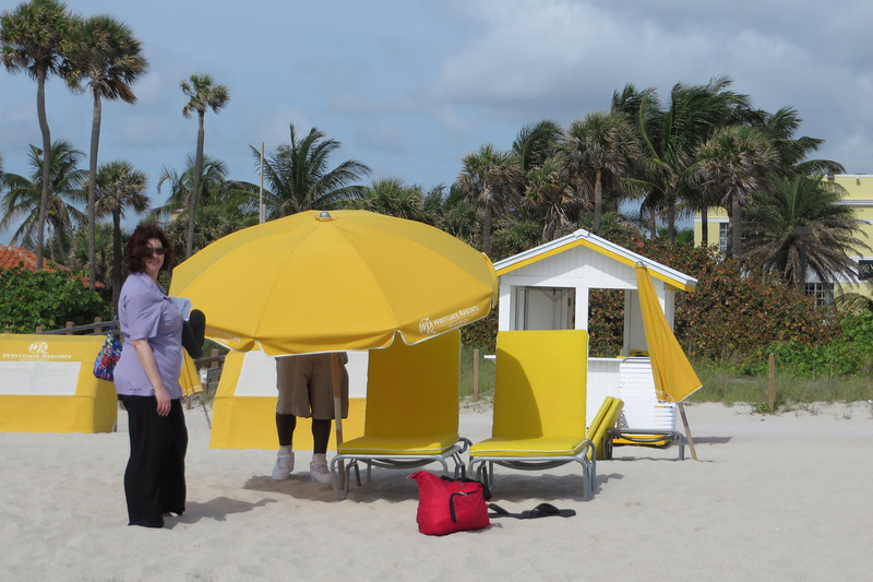 Friday is a beach day.  Sheila waits on the resort beach attendant to set up an umbrella.