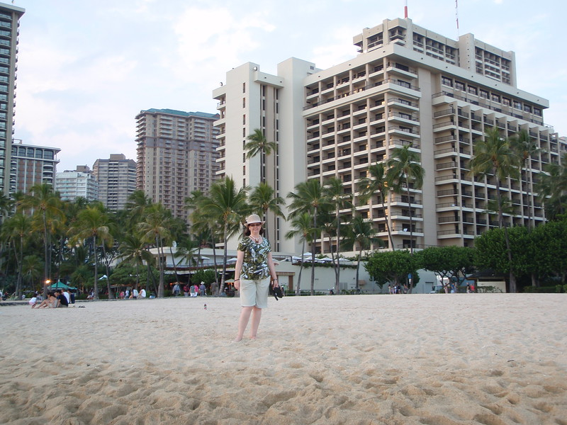 Sheila poses on the beach with the Ali'i tower in the background.