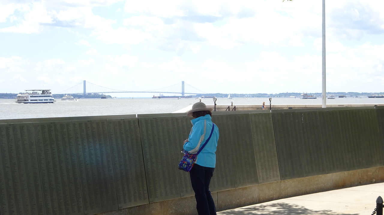 Sheila checks out the Immigrant Wall of Honor.  That's the Verrazano Narrows bridge in the distance.