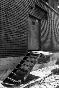 Slanted stairway to a crumbling landing