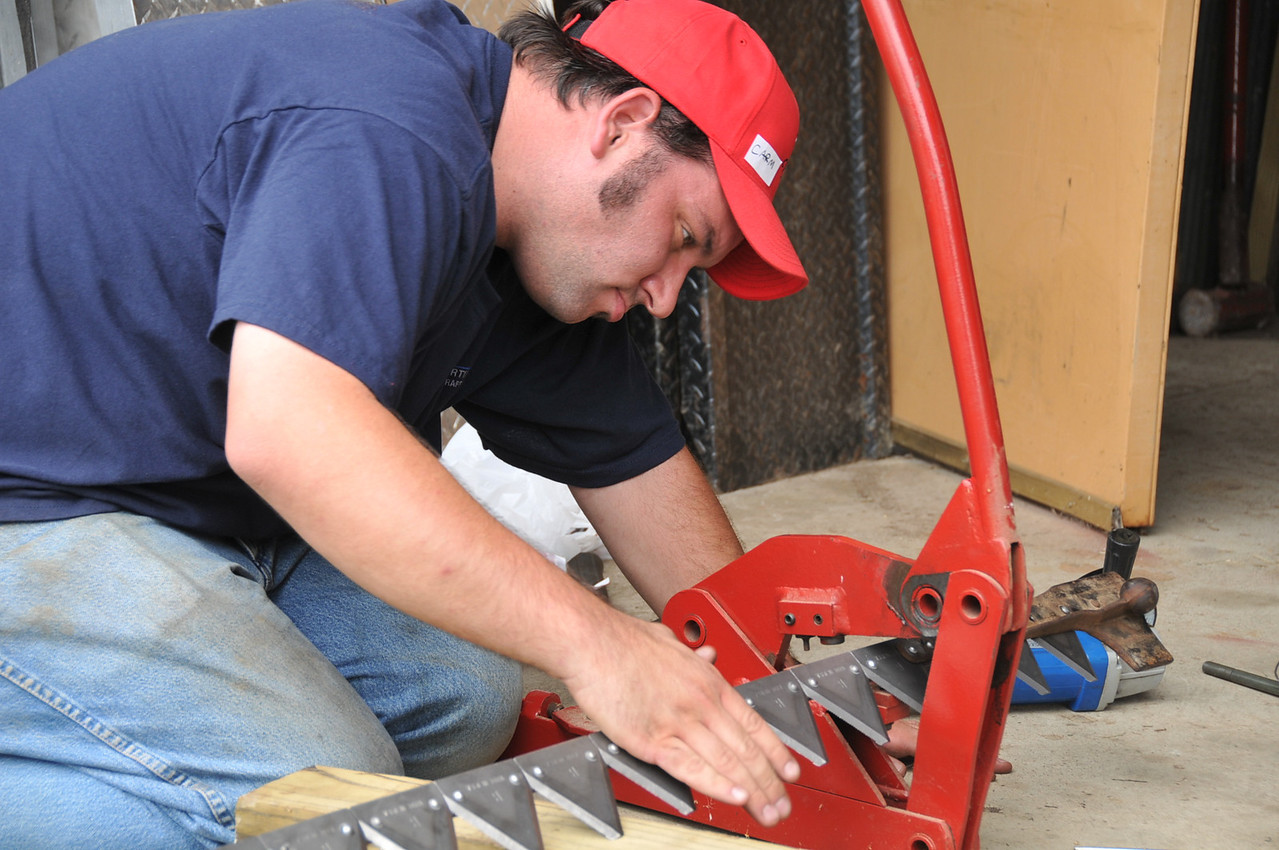 Putting rivets in the sickle bar mower