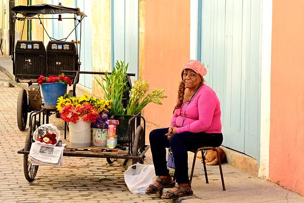 Woman selling flowers on street corner