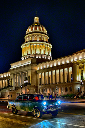 Taxi with headlights and Capitolio building in behind