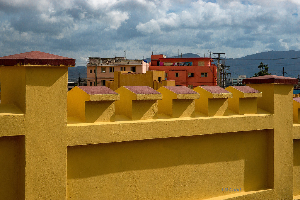Public housing in Santiago de Cuba with the wall of the Moncada Barracks in the foreground.